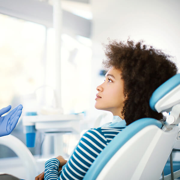 A young woman talking to the dentist