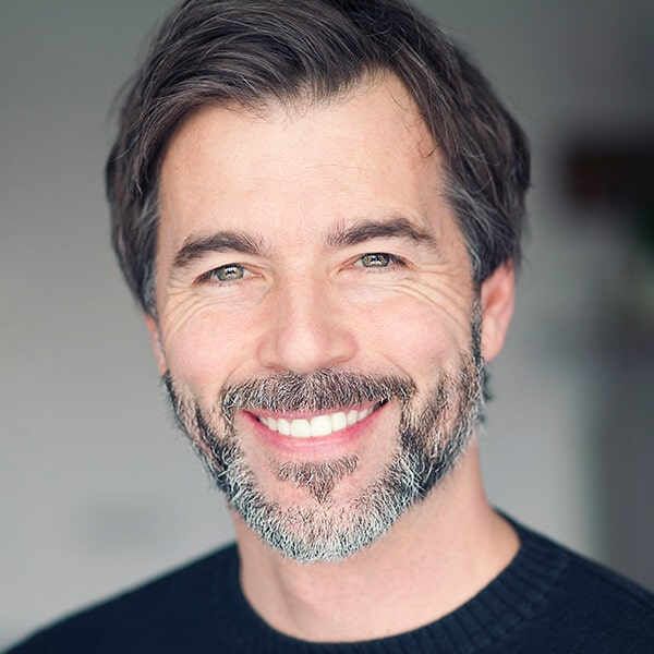 A mature man with a beard smiling