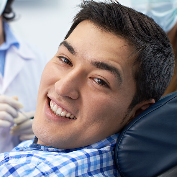 A young man at the dentist smiling