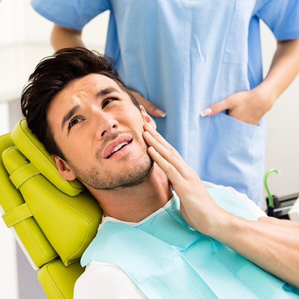 A man at the dentist having severe toothache
